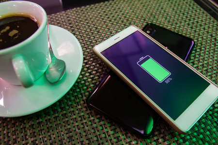 Phone battery wireless charge sharing technology. Wireless charge sharing smartphone in the cafe