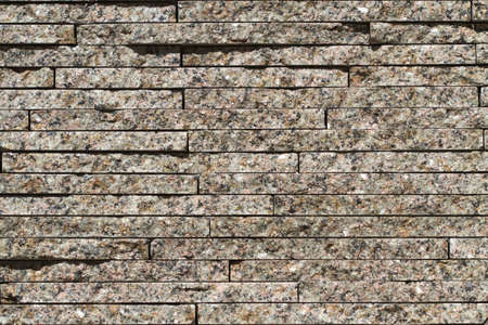 Varicoloured granite blocks of wall for background and texture
