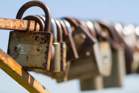 Closeup of many love locks on iron fence on the blue sky background. Locks of love - symbol of lovers. Selective focus. Stockfoto
