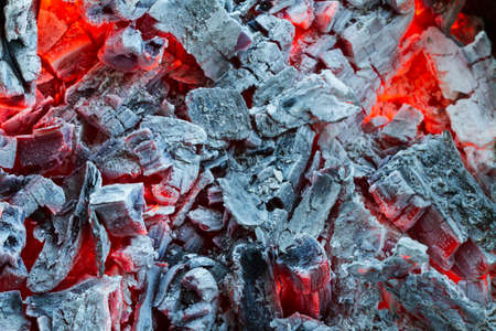 Closeup of smouldering coals, burning charcoal on dark. Ashes in the barbecue.