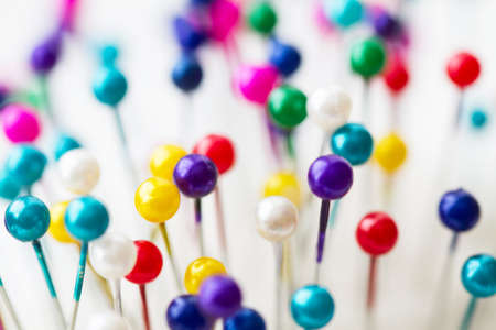 Multicolored sewing pins in the white pin cushion. Close-up 版權商用圖片