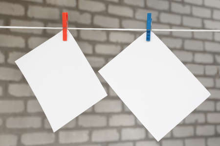 Two white blank sheets of notes with clothespins hanging on bricks background