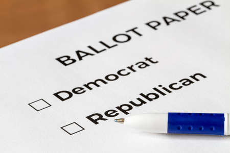 Checklist concept. Closeup of ballot paper with words Democrat and Republican with checkboxes and pen on it.