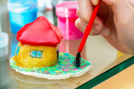 Little girl paints the house from clay or salty dough with acrylic paints. Education concept.