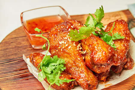 Sesame fried chicken wings with sauce and parsley. Close-up, selective focus Stock fotó