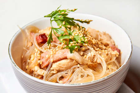 Cellophane noodles with chicken and bacon in a light plate