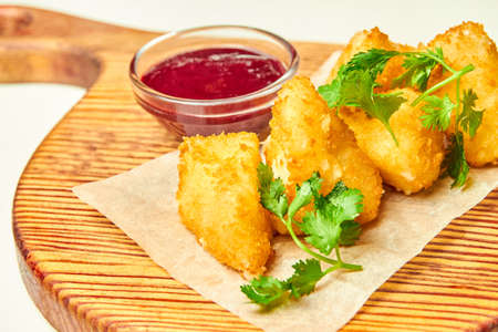 Deep fried cheese nuggets with berry sauce on a wooden board