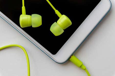 Modern smartphone with lime headphones on light background. Closeup, selective focus Stock fotó