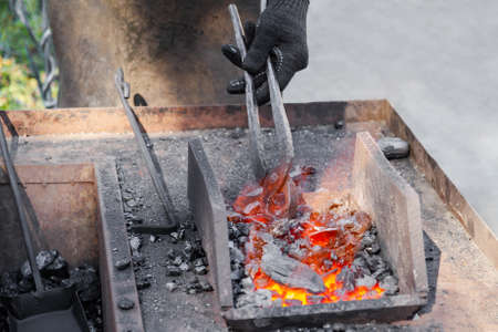 Blacksmith make a horseshoe. Closeup, selective focus