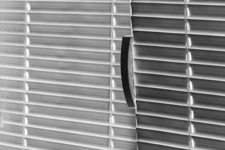 White jalousie background. Closeup, selective focus, black and white photo