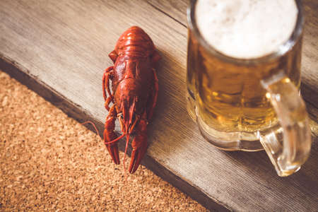 Boiled red crawfish near a cold beer mug. Top view, closeup, selective focus, toned, wooden background