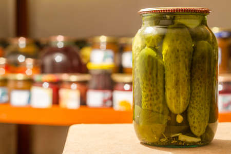 Homemade glass jar with pickled cucumbers in the cellar on the background of shelves with canned vegetables and fruits. Closeup, selective focus Stock fotó