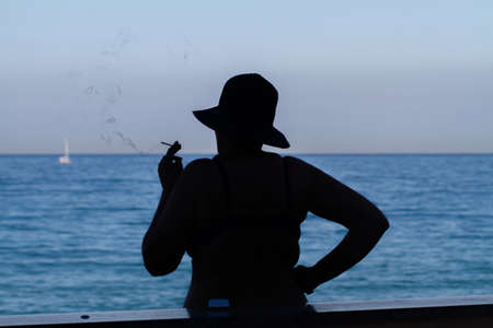Silhouette of a smoking woman in a hat on the background of the sea