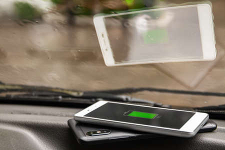 Phone battery wireless charge sharing technology. Wireless charge sharing smartphone in the car in rainy weather Stock fotó