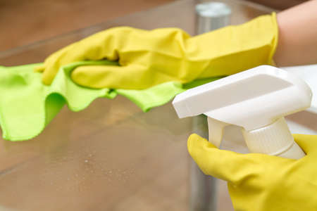 Hands in protective gloves with rag and spray are cleaning the glass coffee table
