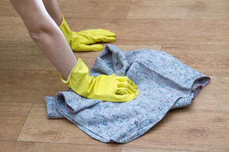 Girl in rubber gloves washes the floor at home with a rag. Concept of housework and housekeeping Stock fotó