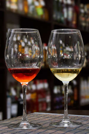 Glass of white and red wine on the background of shelving with bottles of wine