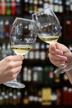 Man and woman clink glasses of white wine on the background of shelving with bottles of wine Stock fotó
