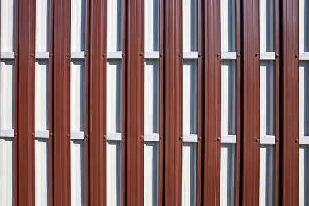 The reverse side of the fence made of corrugated board as a red-white background