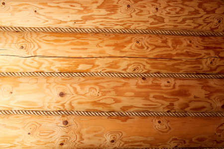 Brown wall as a background from wooden logs with ropes