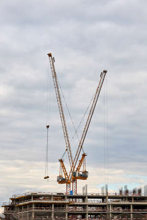 Building under construction and tower cranes against the sky Stock fotó