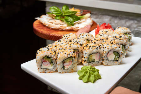 Waiter holds plates with sushi rolls and bacon, onion, mustard. Close-up, selective focus Archivio Fotografico