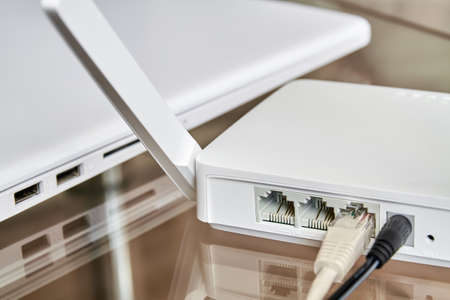 White wireless wifi router near a laptop on a glass table