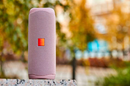 Portable pink wireless speaker in the city on granite surface. Close-up, selective focus