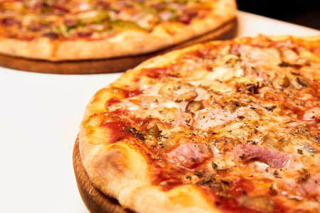 Pizza with cheese, bacon and tomatoes on wooden board. Close-up, selective focus.