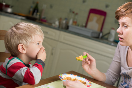 eating dinner: Blond Boy Holds Hand on his Mouth to Stop Eating Stock Photo