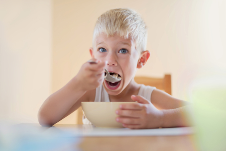 starving: Hungry Kid Starving Eating Corn Flakes Cereals