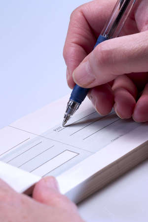 Close-up of hands writing a cheque