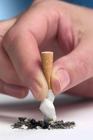 Womans hand stubbing out a cigarette