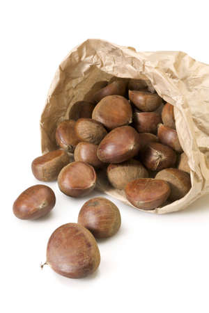 Raw chestnuts spilling from brown paper bag