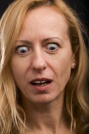 Mature blonde woman with surprised expression looking down