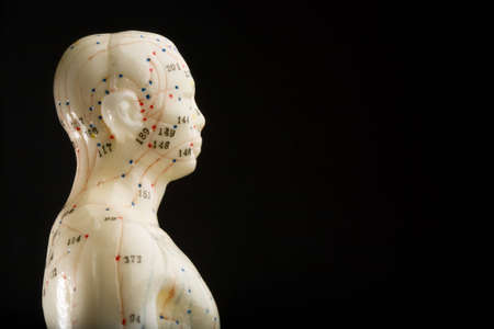 Side view of acupuncturists doll isolated on black with copy space Standard-Bild