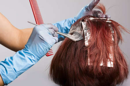 Hairdresser applying colour to customers hair
