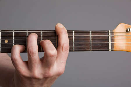Close-up of guitarist playing barre chord on electric guitar Stock Photo
