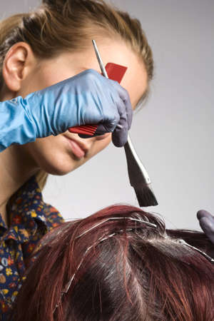 Hair colorist applying color to customers hair