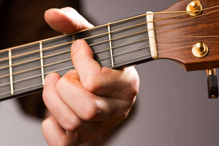 Close-up of acoustic guitar players left hand fingering a chord Stock Photo