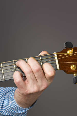 fingering: Close-up of acoustic guitar players left hand fingering a chord Stock Photo