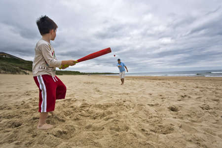 Father and son playing softball on beach Stock Photo
