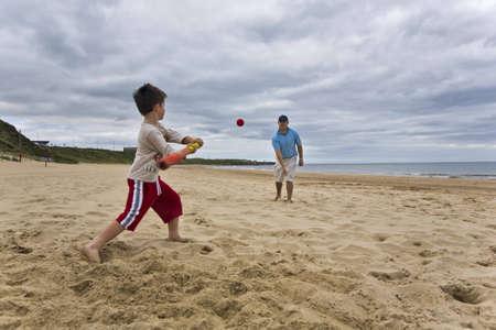 Father and son playing softball on beach Standard-Bild