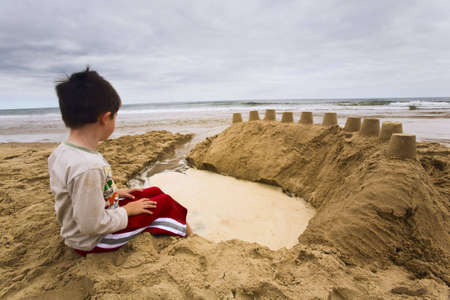 sandcastles: Little boy sitting on a beach next to sandcastles