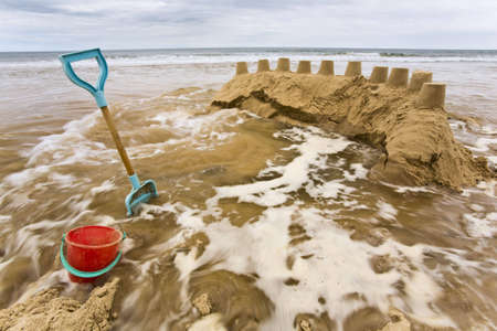 sandcastles: Tide washing over sandcastles at Long Sands Tynemouth Stock Photo