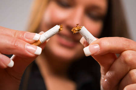 Close-up of woman breaking cigarette with her hands - focus on cigarette