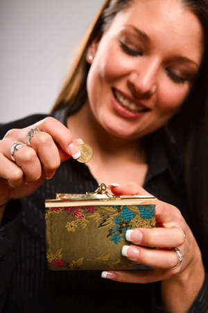coin purse: Woman holding coin purse - focus on coin