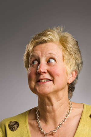 looking away from camera: Mature woman looking away from camera with humorous face Stock Photo