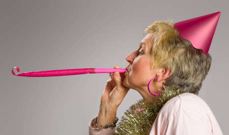 Profile of mature woman blowing party blower Stock Photo