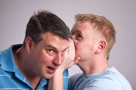 Two gay men gossiping - whispering in ear and listening photo